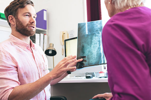 Chiropractor Visually Explaining a Laminectomy Procedure Using and X-Ray
