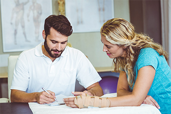 Male Chiropractor Reviews Care Plan at Desk with Happy Female Patient