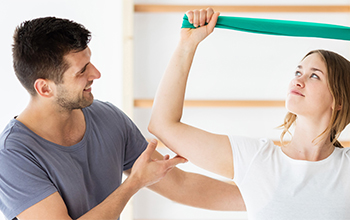 Young Woman Performing Motion Exercises with Resistance Band Under Care of Occupational Therapist in Lieu of Laminectomy