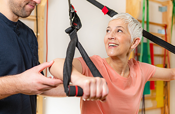 Smiling Woman Performing Exercises with Resistance Bands Under the Supervision of a Physical Therapist as Part of Conservative Treatment for Back Pain in Lieu of Laminectomy