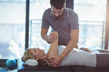Woman Lying on Table While Receiving Chiropractic Adjustment as Part of Conservative Treatment for Back Pain in Lieu of Laminectomy