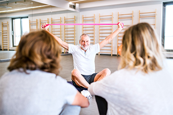 Male Chiropractor Using a Resistance Band to Introduce Posture Workshop Participants to Corrective Stretches