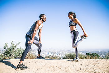 Young Mixed Race Couple Doing Different Runners Stretches to Maintain Good Flexibility and Posture
