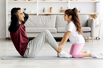 Young Girl and Father Doing Sit-ups Together to Practice Good Posture Habits