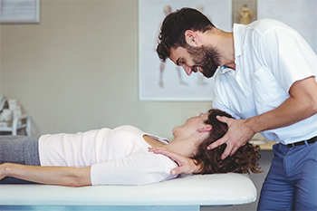 Male Chiropractor Smiling at Relaxed Female Patient During Cervical Spine Adjustment