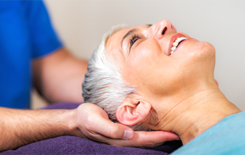 Delighted Female Patient Smiling at Male Chiropractor Following Adjustment to the Cervical Spine