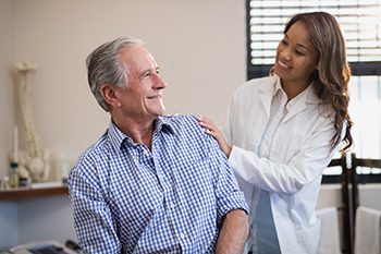 Female Neurological Specialist Meeting Senior Male Patient Referred by Chiropractor for the Initial Exam