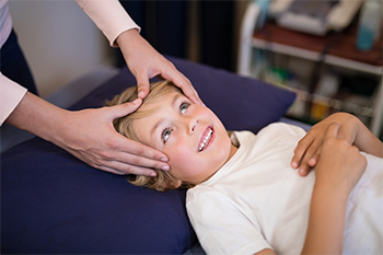 Female Chiropractor Examining Young Boy for Peripheral Vertigo by Stabilizing the Head