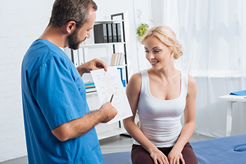 Male Chiropractor Discussing Care Plan with Female Patient Diagnosed with Peripheral Vertigo