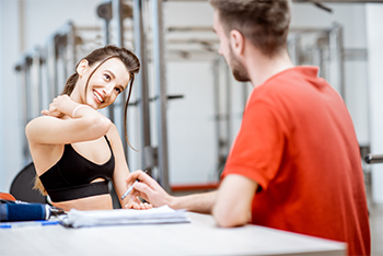 Young Female Athlete Discussing Vertigo with Male Sports Chiropractor