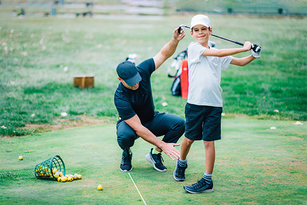 Can Chiropractic Improve Your Golf Game? Young Male Chiropractor Helping Smiling Boy Adjust His Golf Swing Posture