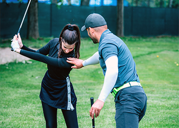 Can Chiropractic Improve Your Golf Game? Male Chiropractor Adjusting Shoulder Posture of Young Female as She Swings a Golf Club