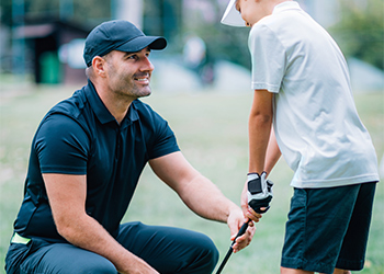 Young Male Chiropractor Helping Adjust Wrist Posture of Young Male Golf Student