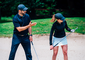 Can Chiropractic Improve Your Golf Game? Young Male Chiropractor Instruction Young Female Golfer on Proper Posture