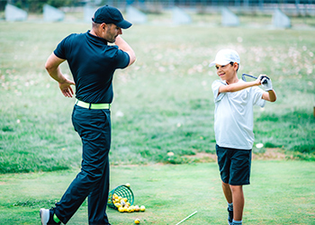 Can Chiropractic Improve Your Golf Game? Young Boy Demonstrating His Improved Flexibility and Golf Swing Following a Chiropractic Adjustment