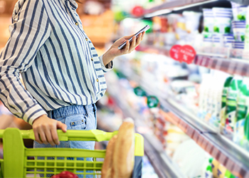 Woman Using Her Cell Phone to Lookup Supplements in the Nutrition Aisle that Support Common Nutrient Deficiencies
