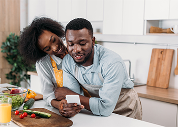 African American Couple Search for Supplements for Common Nutrient Deficiencies While Meal Planning in Kitchen