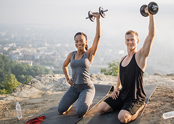 Couple Showing Off Their Strength by Holding Dumbbells Above Their Heads