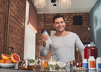 Happy Fit Man Showing Off the Food and Supplements He Uses to Combat Common Nutrient Deficiencies