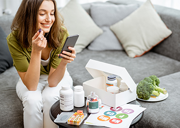 Young Adult Woman Reviewing Fact Sheets About Her New Dietary Supplements from the NIH Office of Dietary Supplements Website