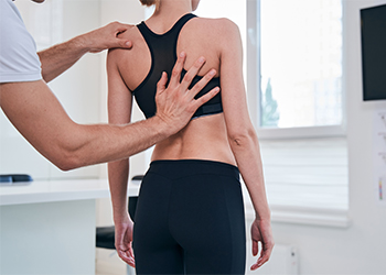 Chiropractor Performing an Evaluation for Lumbar Facet Syndrome on a Female Patient Using Kemp's Test