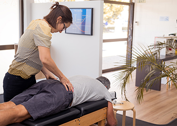 Young Female Chiropractor Performs an Evaluation for Lumbar Facet Syndrome on Middle Aged Male Patient Lying on Adjustment Table