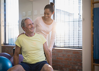 African American Female Chiropractor and Mature Male Patient Sharing a Smile as He Reports Relief from Pain Related to Lumbar Facet Syndrome