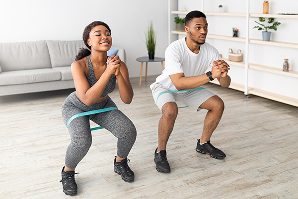 Young African American Couple Training with Resistance Bands to Improve the Biomechanics of Their Squats