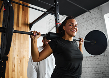 Smiling African American Woman Performing a Squat with a Weight Bar While Being Coached by Male Sports Chiropractor on Proper Biomechanics