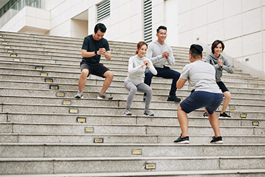 Young Male Chiropractor Coaching a Diverse Group of Individuals on the Proper Biomechanics of a Squat on the Stairs Outside His Practice