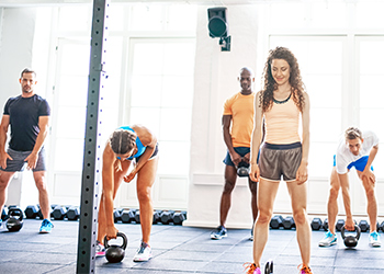 Young Woman Getting in Her Stance While Male Sports Chiropractor Instructs Her Workout Group on the Proper Foot Placement and Biomechanics of a Squat