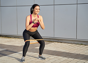 Young Woman with Headphones on Listening to Music with a Hands Folded in Front of Her Chest and a Resistance Band Around Her Thighs Smiling and Performing a Shallow Squat