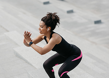 Young African American Woman Performing a Squat While Listening to a Guided Tutorial About Proper Biomechanics and Posture from Her Chiropractor's Podcast