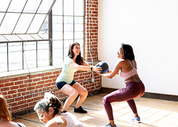 Caucasian and African American Fitness Classmates Practice Passing a Medicine Ball Back and Forth While Squatting to Help Correct Knock Knees