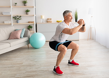 Fit Middle Aged Man with Salt and Pepper Hair Demonstrates Proper Biomechanics of a Squat While Using Resistance Band