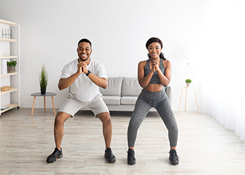 Young African American Couple Smiling and Standing Side by Side with Knees Bent Demonstrate Proper Posture and Biomechanics of a Squat