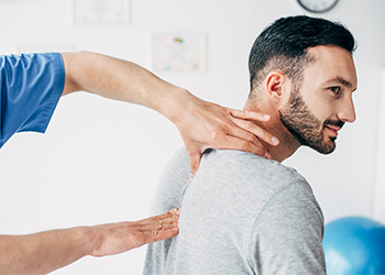 Male Chiropractor Evaluating Cervical Spine of Young White Male Patient Reporting Frequent Suboccipital Headaches