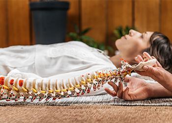 Male Chiropractor Evaluating Posture of Young Asian Female Patient Alongside Spine Model
