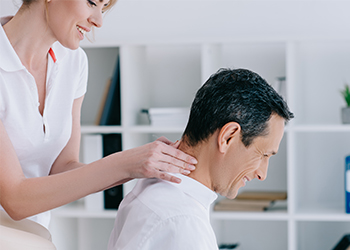 Female Massage Therapist Working Male Patient's Neck to Help Relax the Tight Neck Muscles Contributing to His Suboccipital Headaches