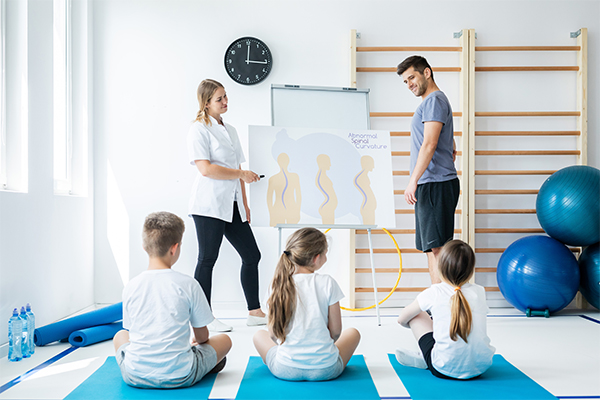 A Mixed Gender Pair of Chiropractic Physicians Explain Scoliosis and Other Spine Problems to a Small Class of Children