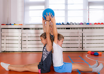Young Girl and Boy Participate in Muscle Strengthening Activity to Help Strengthen the Muscles Supporting their Spines