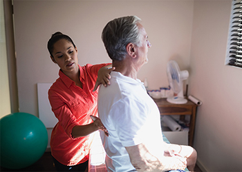 Young Female Latina Chiropractor Evaluates the Spinal Curve of Mature Male Patient for Degenerative Changes