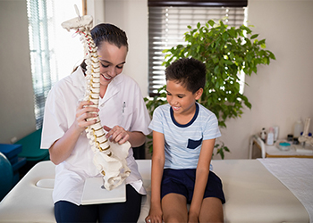 Female Chiropractor Explaining the Curves of the Spine to Her Young Male Patient Using a 3D Model